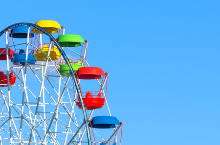 chain swing ride: Wheel of amusement multi-colored cabin on the blue sky background.