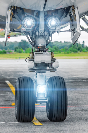 airstrip: Aircraft landing gear and landing lights lights on.