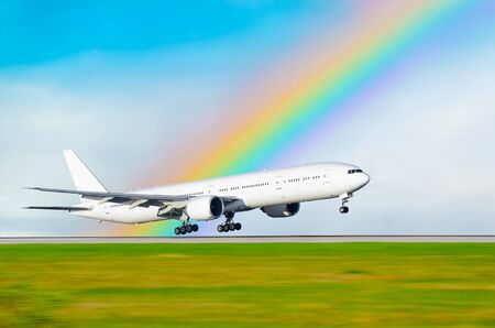 The airplane on the background of the rainbow landed at the airport. Stock Photo