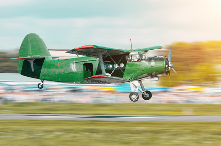 turboprop: Retro green turbo propeller vintage aircraft flying over the car in the airport.