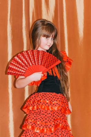 Cute little girl wearing beautiful red and black dress with matching headband, using hand fan, studio background. Stock Photo