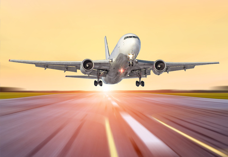 Big airplane in motion take off the evening sky sunset sunrise sun airport Stock Photo