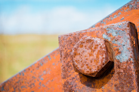 Old rusty bolts and steel nuts in the background a blurred sky and a field Stock Photo