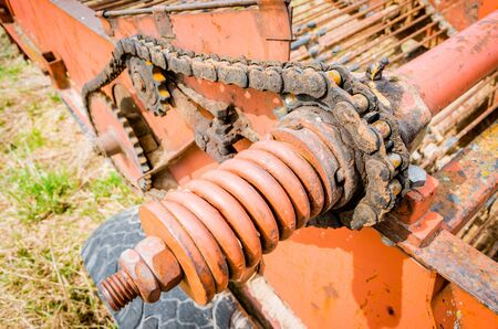 Spring gear and old chain in oil on the mechanism of old rural machinery Stock Photo