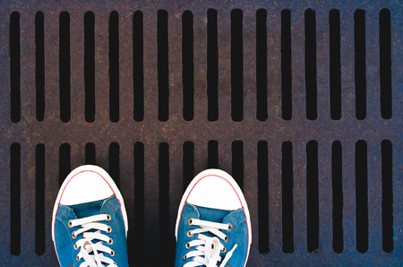metal grate: Sneakers on grunge background lattice sewer for a walk in the city