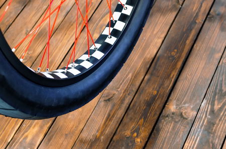 spokes: Wheel of a stylish bicycle with a black and white rim and a black rubber tire on a stylish wooden background