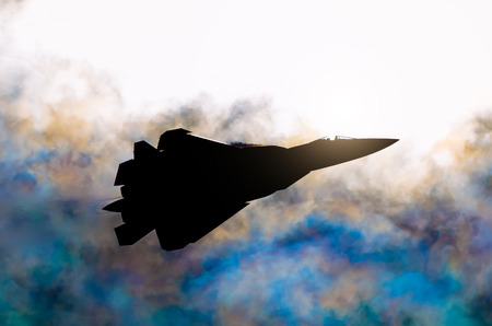 Silhouette of a military fighter against the background of the sun and rainbow clouds