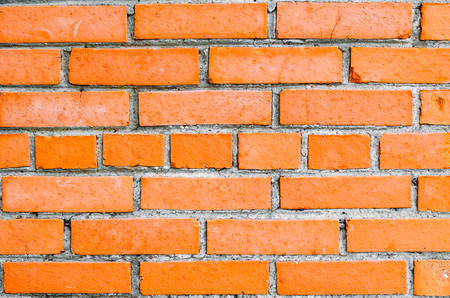 weathered: Brick wall of orange brick, in the middle row of bricks with butt
