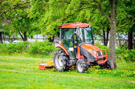 빨간색 트랙터 및 잔디 깎는 기계, 공원에서 골목에 잔디를 가위