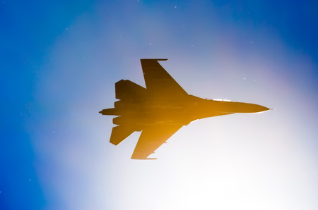 Silhouette of a military fighter sun lights blue sky