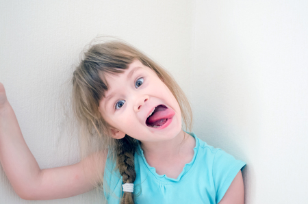 Little caucasian cheerful girl hamming fooling around and showing tongue Stock Photo