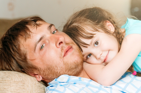 familia abrazo: The daughter lies on her father and rests, embrace family