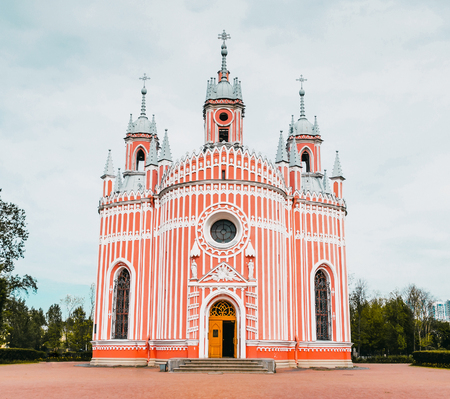 Red church with white strips in Gothic style Stock Photo