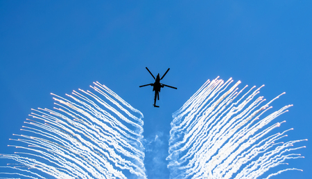 Helicopter smoke a rocket, in the sky a heat trap Stock Photo