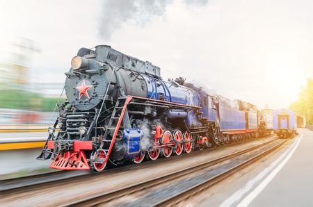 Vintage black steam locomotive train rush railway station. Concept of tourism is a retro journey by train