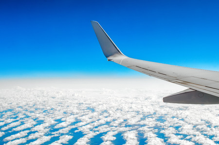 Beautiful classic view of the porthole during a flight by plane, clouds of blue sky and earth