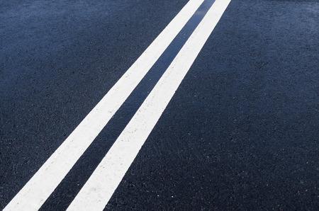 Double solid white line on wet asphalt Stock Photo