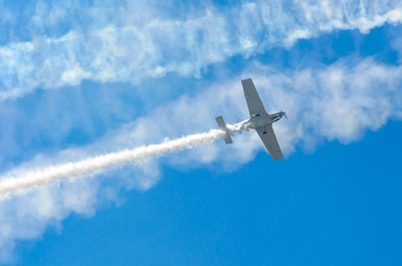 navy blue background: White turboprop airplane with a trace of white smoke against a blue sky