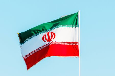Waving colorful Iran flag on blue sky