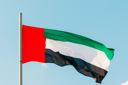 Waving colorful United Arab Emirates flag on blue sky