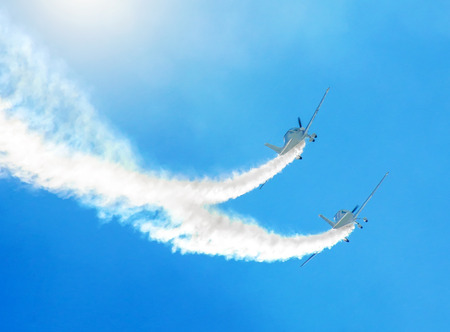 Two white turboprop airplane with a trace of white smoke against a blue sky 写真素材