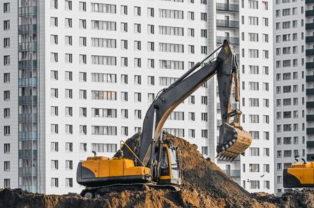 sand quarry: Excavator work on the ground on background of multi storey houses