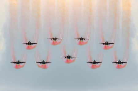 Nine fighter jets fly together with red smoke Stock Photo
