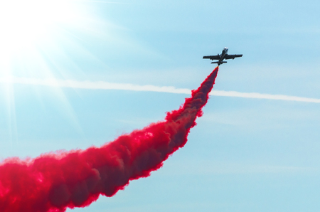 Airplane fly in zigzags with a red trail smoke in the sky