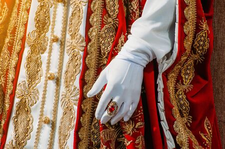 Clothes of a historical imperial woman with red elements, a hand in white gloves and a ring with a precious stone Stock Photo
