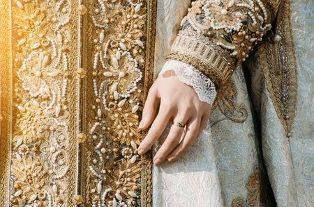 empress: Clothes of a historical imperial woman with pastel tones, a hand with a ring with a precious stone Stock Photo