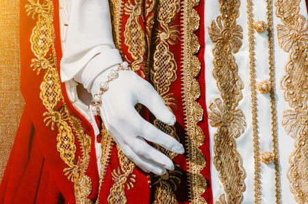 Clothes of a historical imperial woman with red elements, a hand in white gloves