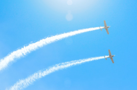 Light engine airplane with a trace of white smoke fly in groups in the blue sky with sunlight and glare