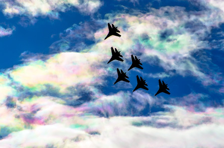 Fighter jet group flies in the clouds and iris multicolored sky Stock Photo