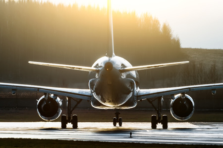 Silhouette of an aircraft illuminated by the sun contours contrast on a runway Фото со стока