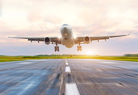 Passenger airplane landing at sunset on a runway Stock Photo