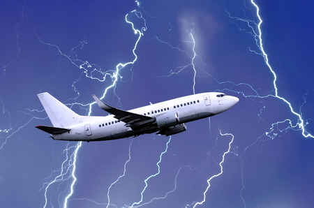 White passenger airplane takes off during a thunderstorm night lightning strike of rain, bad weather Stock Photo
