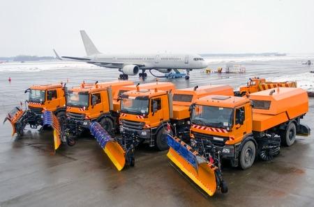 Sneeuwruimen machine geparkeerd in een rij op de achtergrond van een passagiersvliegtuig op de luchthaven