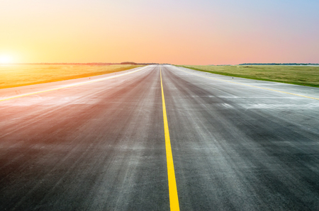 Asphalt road with a dividing strip in the horizon at sunset Stock Photo