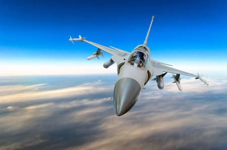 Military fighter jet against a blue sky with a backlight from below