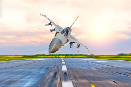 Military fighter jet flies at high speed over the taxiway at the airport Stock Photo