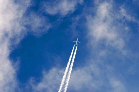 Airplane contrail clouds against the blue sky
