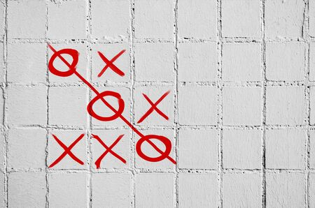 The game of crosses toes on a concrete wall of white tiles