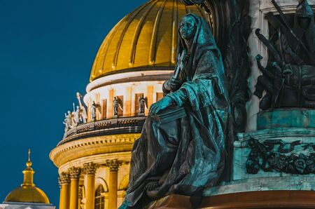 Night view of the ancient statues of stucco and the dome of St. Isaacs Cathedral Saint-Petersburg