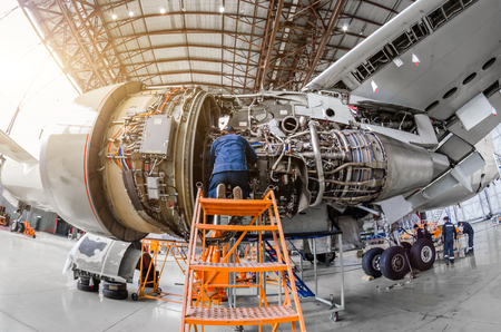 Specialist mechanic repairs the maintenance of a large engine of a passenger aircraft in a hangar Reklamní fotografie - 87423628