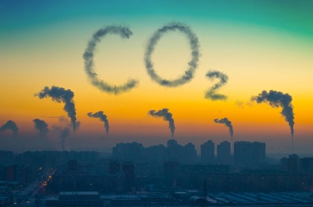 Vista nocturna del paisaje industrial de la ciudad con emisiones de humo de las chimeneas al atardecer. Inscripción CO2