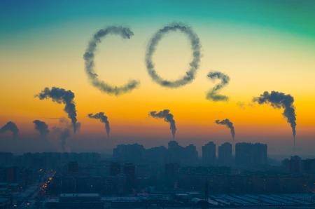 Vue de soirée du paysage industriel de la ville avec des émissions de fumée des cheminées au coucher du soleil. Inscription CO2