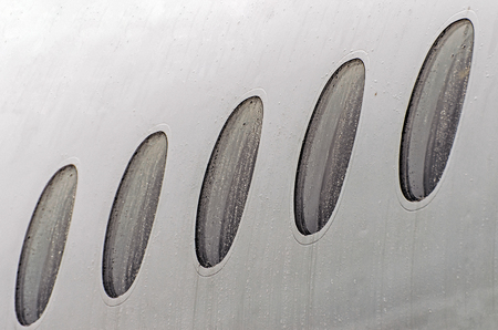 Porthole windows of an airplane wet weather in rain drops of water, close-up