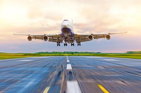 Avion de passagers atterrissant au coucher du soleil sur une piste
