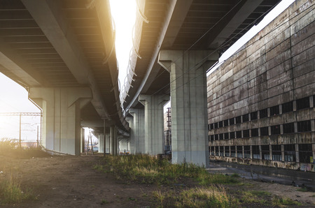 High-speed highway on high supports, near the old factory, warehouse