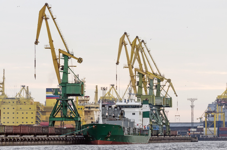 unloading: Cargo freight ship and cargo container working with crane at port area,Logistic Import Export